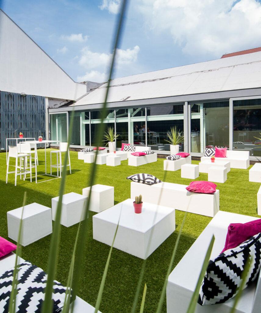Belle terrasse emménagée pour événements extérieurs, pelouse et fauteuils