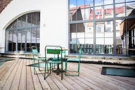 Terrasse en bois aménagée avec grandes baies vitrées, à la Tricoter